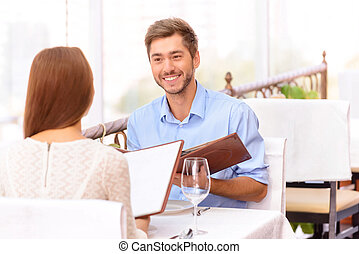 Loving couple looking through menu in the restaurant