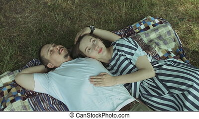 Portrait of joyful pregnant couple lying on picnic blanket in summer park and chatting. Attractive family expecting baby resting on blanket and discussing future plans while enjoying leisure in nature