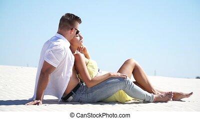 Loving couple lying on the sand in the desert