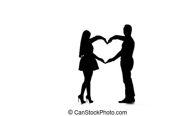 Loving couple makes a heart shape with the help of hands. Silhouette. White background. Slow motion