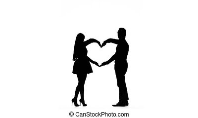 Loving couple makes a heart shape with the help of hands. Silhouette. White background with