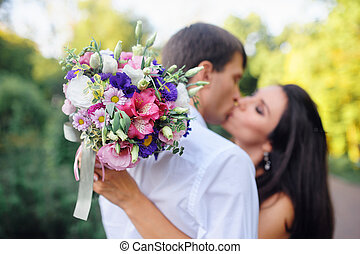 loving couple man and woman together, with a bouquet in the foreground
