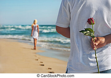 loving couple, man with rose waiting his woman on the sea...