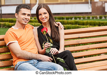 Loving couple on the bench. Beautiful young loving couple sitting close to each other on the bench and smiling