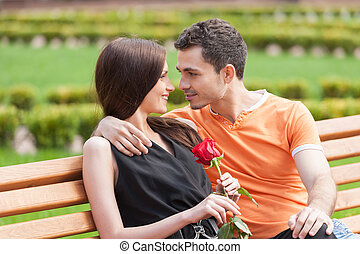 Loving couple on the bench. Beautiful young couple sitting close to each other on the bench and looking at each other