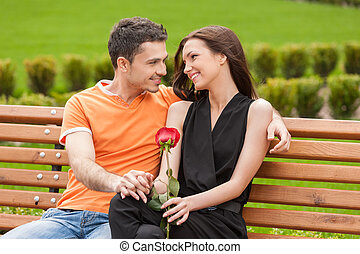 Loving couple on the bench. Cheerful young couple sitting close to each other on the bench and looking at each other