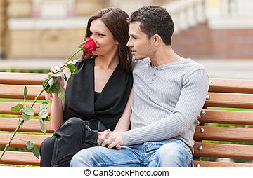 Loving couple on the bench. Cheerful young couple sitting close to each other and looking away
