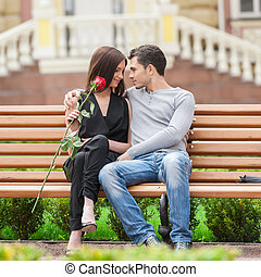Loving couple on the bench. Cheerful young couple sitting close to each other and smiling