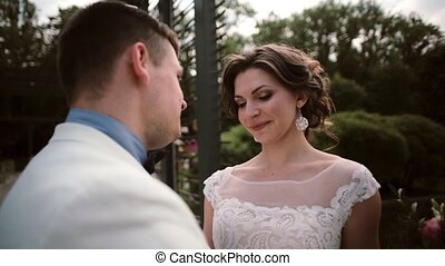 Loving couple on their wedding day in summertime, kissing and tenderly looking at each other. Happy bride and groom.
