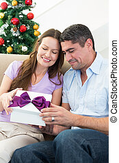 Loving couple opening Christmas gift