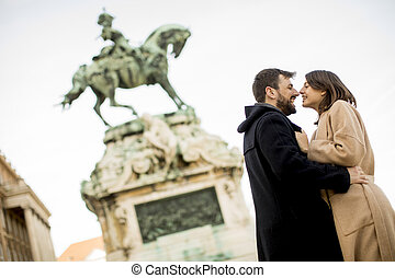 Loving couple outdoor with monument in background in Budapest, Hungary