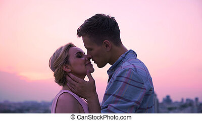 Loving couple passionately kissing, meeting dawn on roof of high-rise building