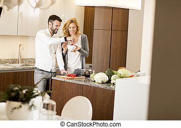 Loving couple prepating vegetarian food in the modern kitchen