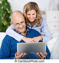 Loving couple reading information on a tablet-pc