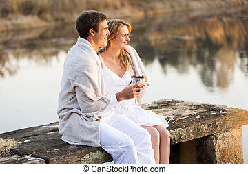 loving couple relaxing on a pier and wrapped in blanket at sunset
