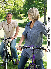 Loving couple riding bicycles in park