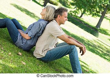 Loving couple sitting back to back