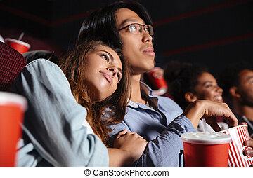 Loving couple sitting in cinema watch film