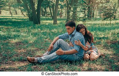 Loving couple sitting in summer park