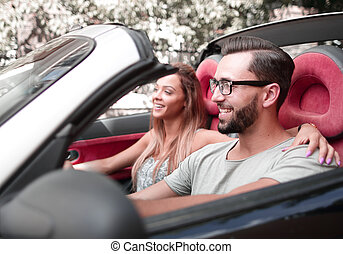 loving couple sitting in the front seat of a convertible car