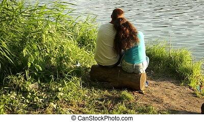 Loving couple sitting on a log near