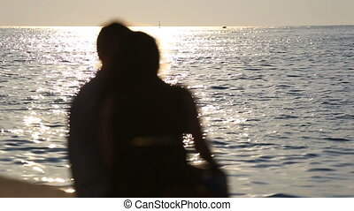 Loving couple sitting on promenade near sea in evening, view...