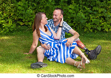Loving couple sitting on the grass looking affectionately...