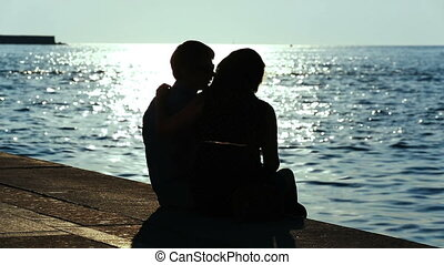 Loving couple sitting on the promenade near the sea in the evening