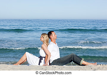 Loving couple sitting on the sand