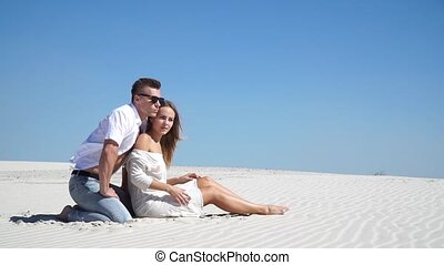 Loving couple sitting on the sand in the desert