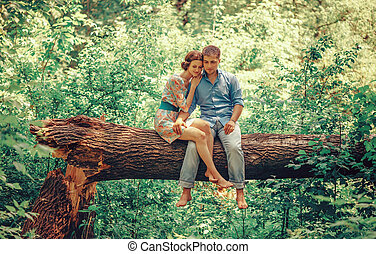 Loving couple sitting on tree in summer
