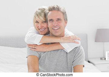 Loving couple smiling at camera at home in bedroom