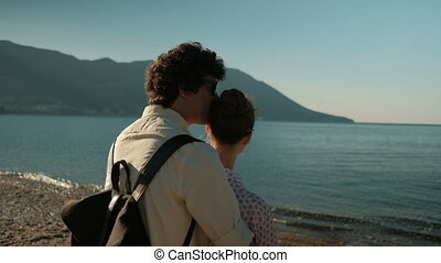 Loving couple standing by sea shore in summer day.