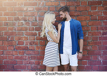 Loving couple standing in front of brick wall