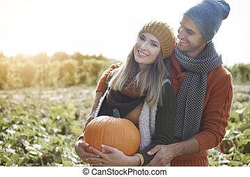 Loving couple standing in the pumpkin field