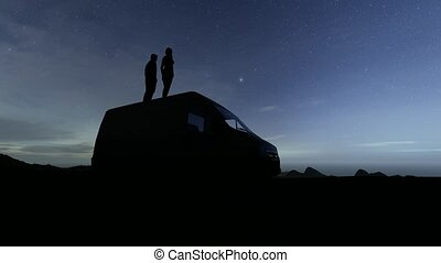Loving couple stands by car and looks at the starry night 4k