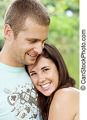 loving couple - a loving couple hugging each other and...