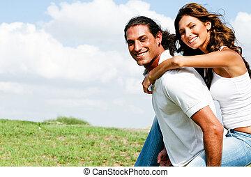 Loving couple - Smiling couple enjoying piggyback ride on...