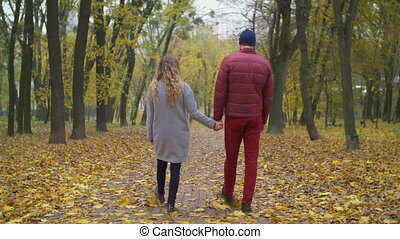 Loving couple taking a stroll in autumn nature - Rear view...