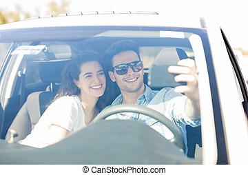 Loving couple taking selfie in a car