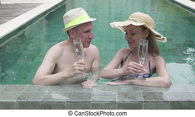 Loving couple the man and the woman have a rest in the pool in the tropical resort also drink white wine