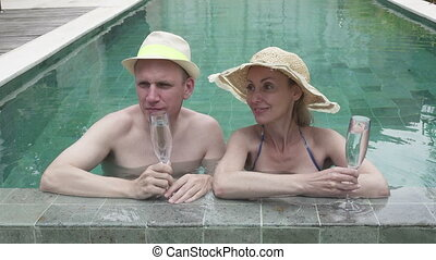 Loving couple the man and the woman have a rest in the pool in the tropical resort also drink white wine,