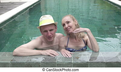 Loving couple the man and the woman have a rest in the pool in the tropical resort ,