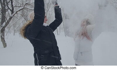 loving couple throwing snow in the snow-covered forest -...