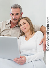 Loving couple using laptop on sofa