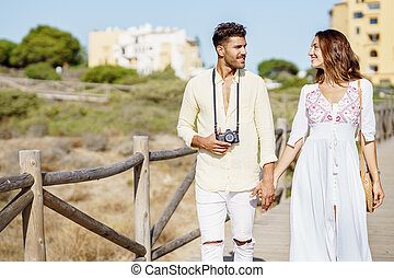 Loving couple walking along a wooden path towards the beach in a coastal area.
