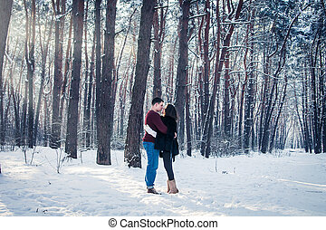 Loving couple walking in winter forest. Young people having good time together