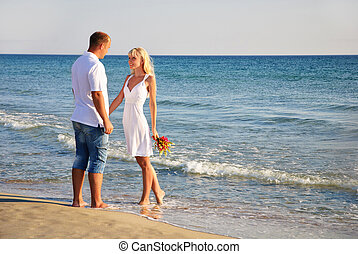 loving couple walking on the sea beach at summer with the...