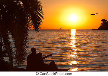 Loving couple watching beautiful sunset on seashore