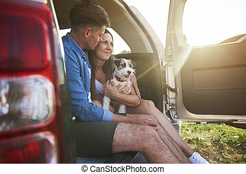 Loving couple with dog enjoying the view in summertime